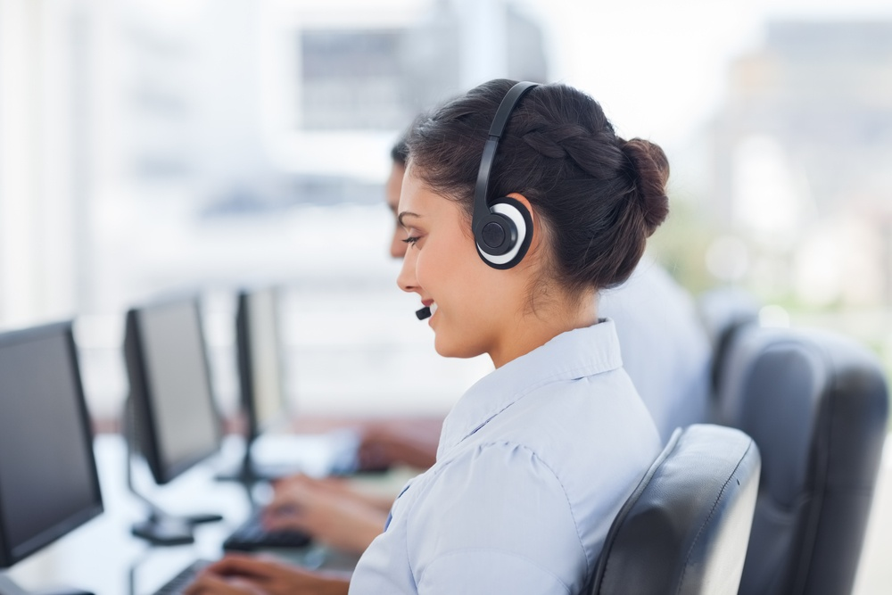 Attractive brunette working in a call centre with her headset